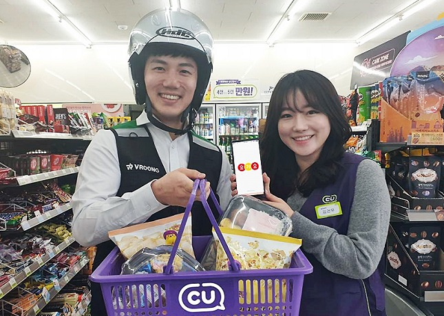 This undated photo, provided by BGF Retail, shows a deliveryman and a staffer demonstrating the delivery service provided by the group's convenience store chain CU.