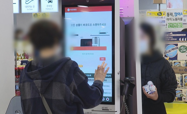 This image provided by Yonhap News TV shows people using kiosk machines at a store.
