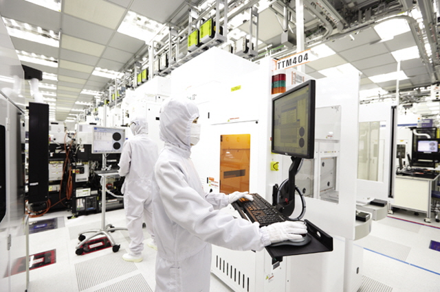 This undated photo provided by SK hynix Inc. shows workers at the company's chip plant in Icheon, south of Seoul.
