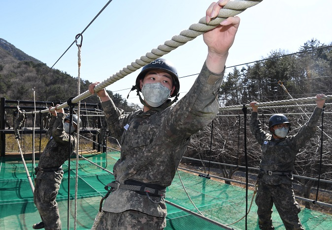 In this file photo, taken on March 13, 2020, and provided by the Navy, recruits undergo combat training while wearing masks at a boot camp of the Naval Education and Training Command in the southeastern city of Changwon amid the nationwide spread of the coronavirus.