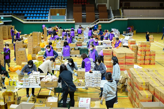 Volunteers sort aid packages made with donations for delivery to the city's underprivileged citizens, in this file photo provided by the Suncheon City Hall.