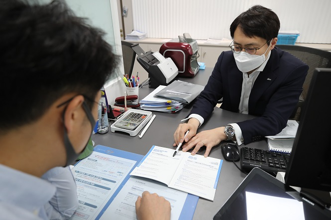 In the photo, taken April 6, 2020, a customer (L) holds an interview with a bank official in Seoul for a special low-interest loan designed for local businesses hit by the new coronavirus outbreak. (Yonhap)