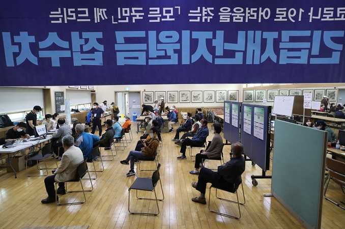 Residents wait while keeping a distance from each other to apply for emergency disaster relief funds at a community center in Seoul on May 18, 2020. (Yonhap)