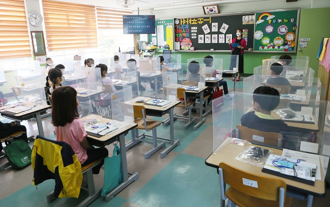 Elementary school students sit at desks fitted with plastic dividers in Incheon, west of Seoul, on May 27, 2020. (Yonhap)