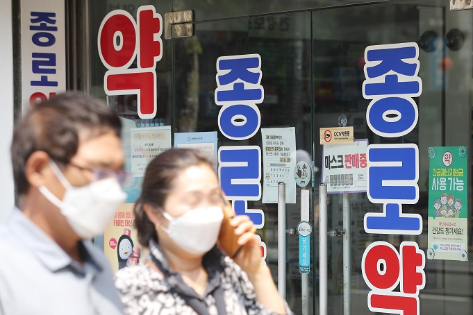 Pedestrians wearing face masks walk past a pharmacy in the central Seoul ward of Jongno on May 31, 2020. (Yonhap)