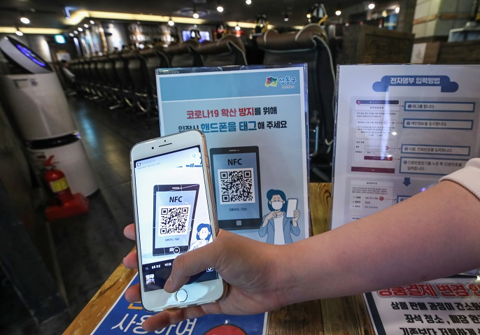 An employee at an internet cafe in Seoul demonstrates the scanning of a patron's quick response (QR) code on June 1, 2020. (Yonhap)