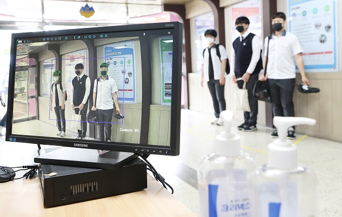 High school pupils have their body temperatures checked before heading into classrooms at Gwacheon High School in Gwacheon, south of Seoul, on June 3, 2020. (Yonhap)