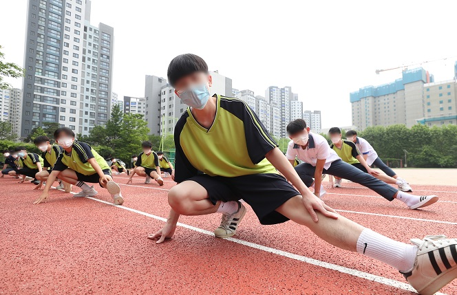 Students stretch during a physical education class at Gwacheon High School in Gwacheon, south of Seoul, on June 3, 2020, when South Korea implemented the third phase of school reopening for high school first graders, middle school second graders and elementary school third and fourth graders. (Yonhap)