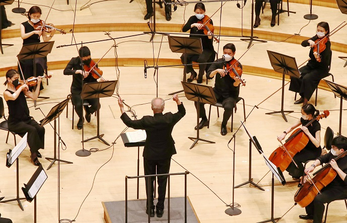 This file photo from June 5, 2020, shows a rehearsal of the Seoul Philharmonic Orchestra with members seated far apart and wearing masks at the Lotte Concert Hall in eastern Seoul. (Yonhap)