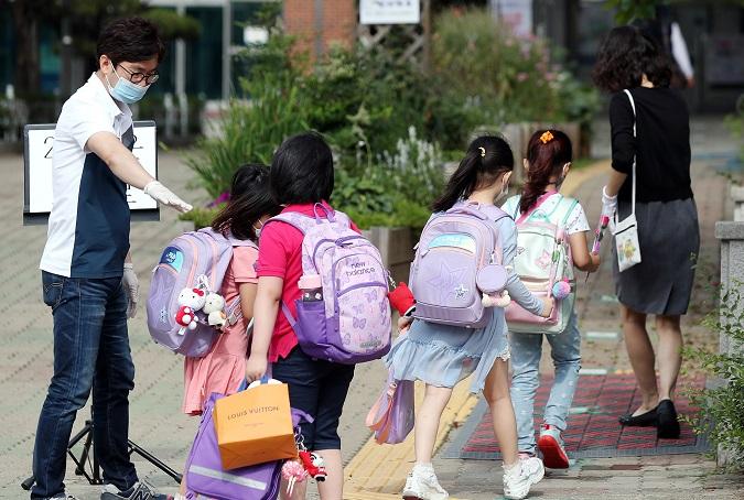 Pupils enter school in Bucheon, Gyeonggi Province, on June 11, 2020. (Yonhap)