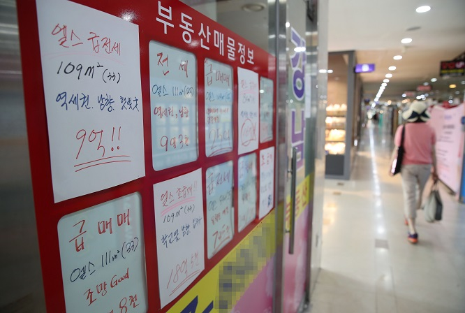 This photo, taken on June 14, 2020, shows signs with bidding prices for housing transactions put up at a real estate agency in Seoul. (Yonhap)