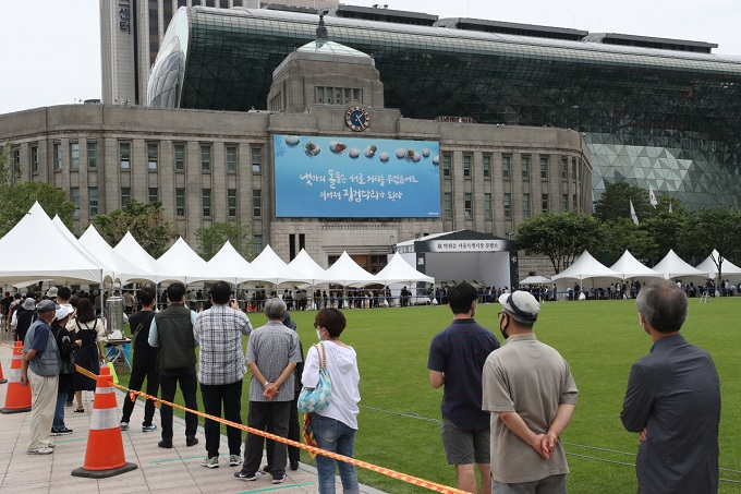 Citizens wait in line to mourn at a memorial altar set up in front of Seoul City Hall in the city center for late Mayor Park Won-soon on July 12, 2020. (Yonhap)