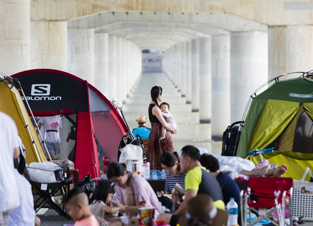 People rest along the Han River flowing through the center of Seoul on Aug. 1, 2017, as sweltering heat hits South Korea. (Yonhap)