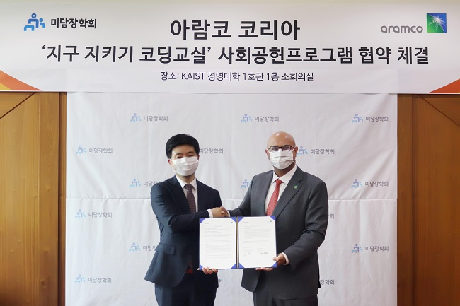 This photo, provided by Aramco Asia Korea, shows its Representative Director Fahad A. Al-Sahali (R) shaking hands with Jang Neung-in, MIDAM's standing director, after signing a partnership agreement for coding programs at the KAIST College of Business in Seoul.