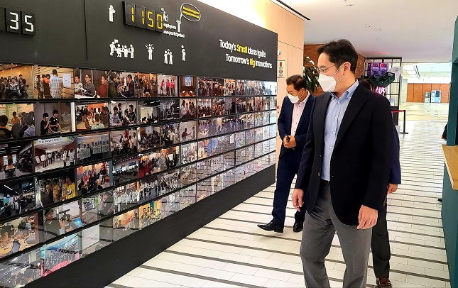 In this photo provided by Samsung Electronics Co. on July 6, 2020, Samsung Electronics Vice Chairman Lee Jae-yong (R) looks at photos of the company's in-house startup incubation program C-Lab in Suwon, south of Seoul.
