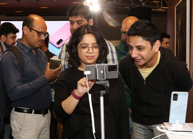 This photo, provided by Samsung Electronics Co. on March 6, 2020, shows Indian consumers inspecting the company's Galaxy S20 smartphones at an event in Gurugram, India.