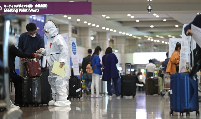 This photo taken on May 3, 2020, shows a health official speaking with a tourist at Incheon International Airport in Incheon, west of Seoul. (Yonhap)
