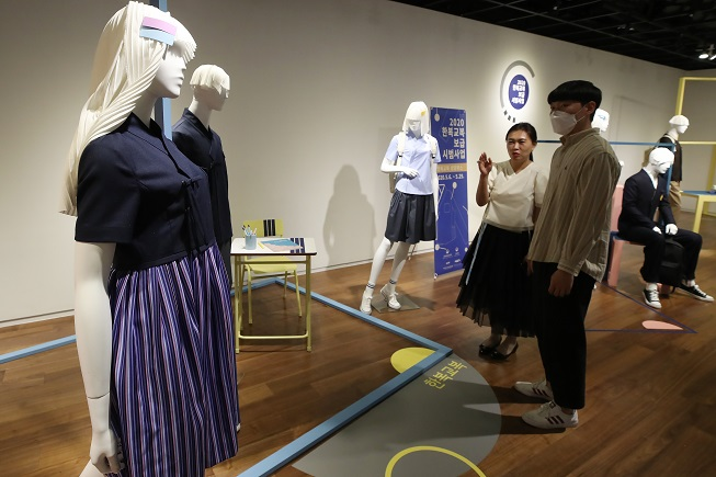 "In this file photo, employees of the Hanbok Advancement Center check displays of school uniforms that use modern designs based on ""hanbok,"" traditional Korean clothes, at a gallery in Seoul on May 7, 2020. (Yonhap)"