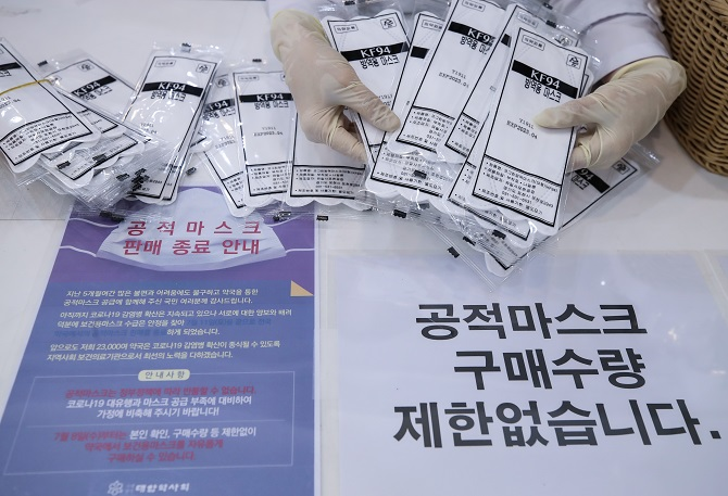 A pharmacist counts masks supplied under a state-led mask rationing system at a pharmacy in central Seoul on July 8, 2020. (Yonhap)