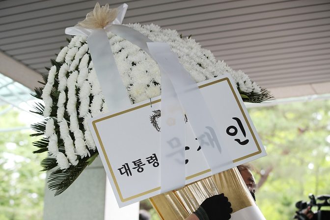 A man carries condolence flowers sent by President Moon Jae-in to the funeral home of Seoul Mayor Park Won-soon on July 10, 2020. (Yonhap)