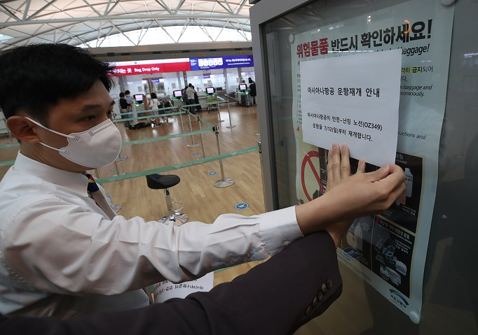 An employee at Incheon International Airport, west of Seoul, posts a sign that shows Asiana Airlines Inc., South Korea's second-biggest carrier by sales, has resumed flights to the Chinese city of Nanjing. Flights to Nanjing had been suspended since late March due to concerns over the new coronavirus. (Yonhap)