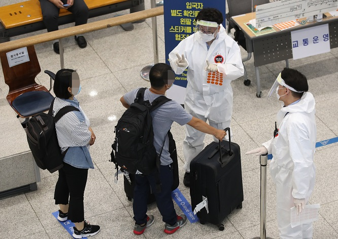 Arrivals receive instructions from health officials at Incheon International Airport, west of Seoul, on July 12, 2020. (Yonhap)