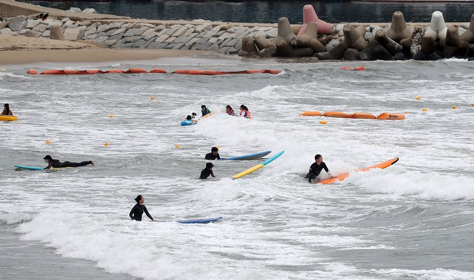 Vacationers enjoy surfing at a beach in Yangyang, 215 kilometers east of Seoul, on July 12, 2020. (Yonhap)