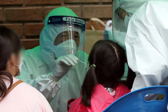 Children are checked for the coronavirus at a screening station set up at a kindergarten in Yeongtong Ward in Suwon, 46 kilometers south of Seoul, on July 13, 2020. (Yonhap)