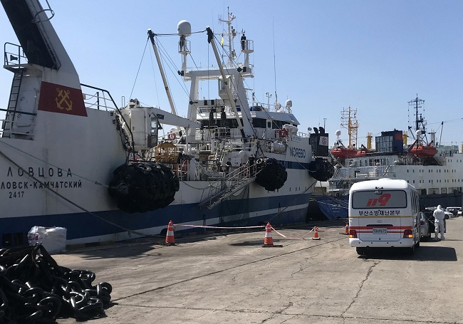 This photo, provided by fire service authorities in the southeastern port city of Busan on July 17, 2020, shows firefighters transferring Russian sailors infected with COVID-19 to a hospital for treatment.