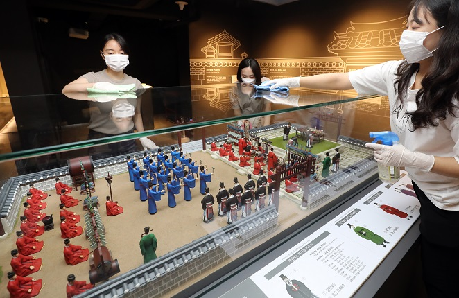 This file photo shows staffers at Seonjam Museum in central Seoul cleaning an exhibit piece with disinfectants on July 20, 2020, two days ahead of the reopening of national cultural facilities in the metropolitan area that have been shut down for months due to the coronavirus, including museums, art centers and libraries. (Yonhap)