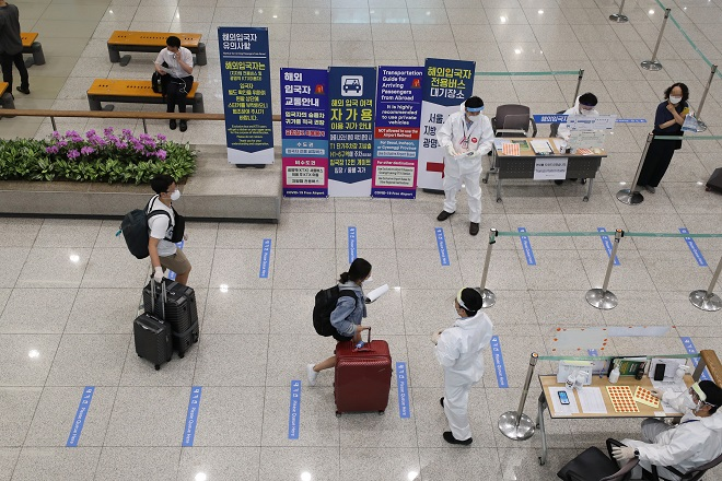 This photo, taken on July 23, 2020, shows health workers guiding arrivals at Incheon International Airport in Incheon. (Yonhap)