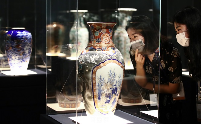 Visitors at the National Palace Museum of Korea in Seoul on July 28, 2020, observe a Chinese-made porcelain vase that was exported to France and later brought to Korea during the late 19th century. (Yonhap)
