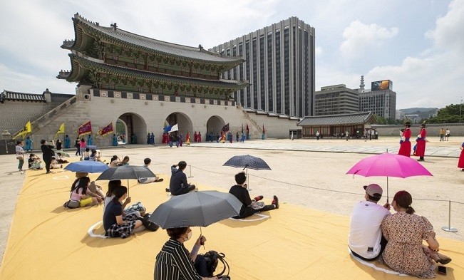 Visitors watch a royal guard-changing ceremony while sitting apart at Gyeongbok Palace in Seoul on July 30, 2020. (Yonhap)