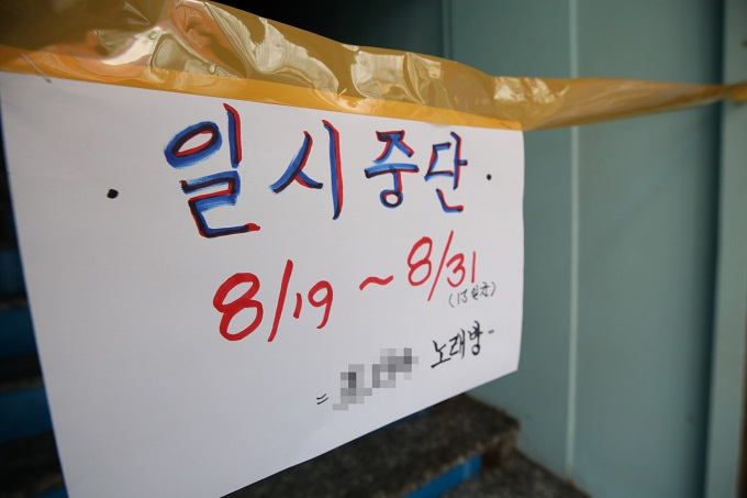 A sign in front of a karaoke room in South Korea says business is suspended till the end of August. (Yonhap)