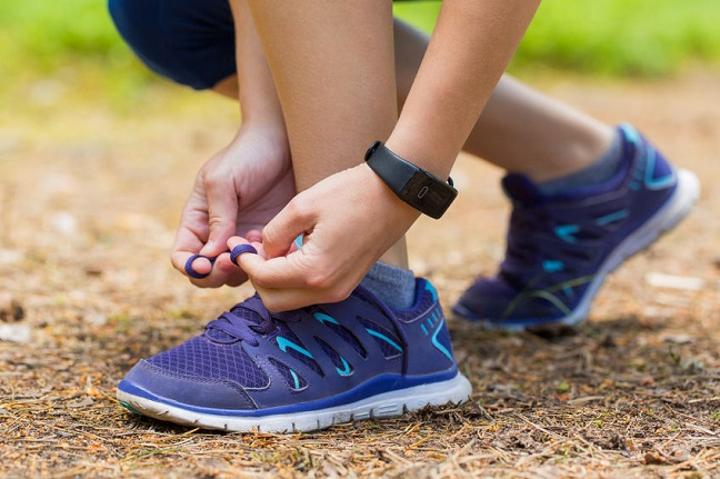 Close up of woman tying shoe laces in summer workout.