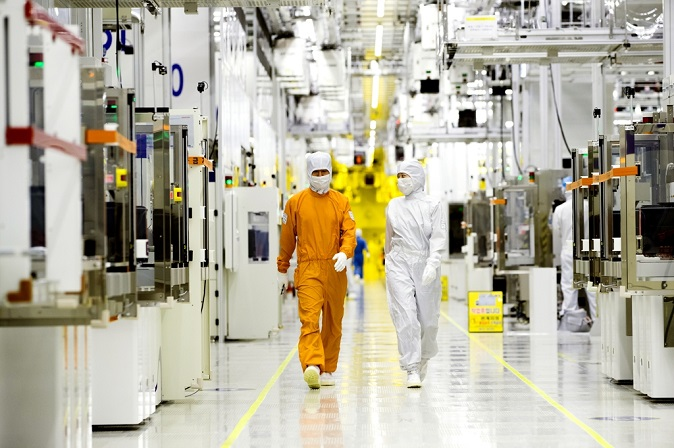 Two employees of Samsung Electronics Co. check equipment of the clean room of its semiconductor production facility in this photo provided by the company on May 15, 2019.