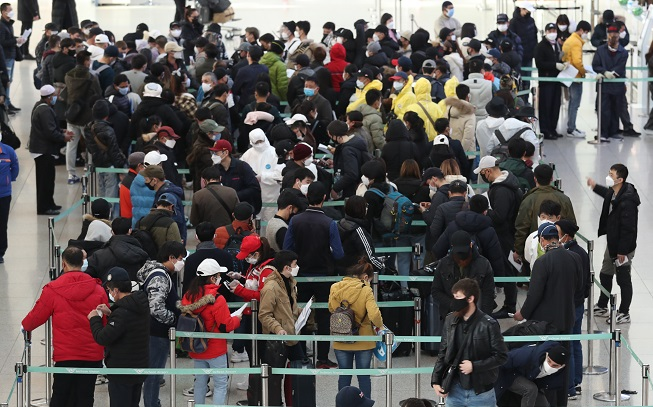 This file photo, taken March 6, 2020, shows illegal immigrants queuing up at Incheon International Airport, west of Seoul, to voluntarily leave the country. (Yonhap)