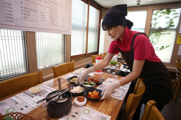 A staff member wearing a protective mask serves dishes at a restaurant in Gwangju, 330 kilometers south of Seoul, in this file photo taken on July 21, 2020. (Yonhap)