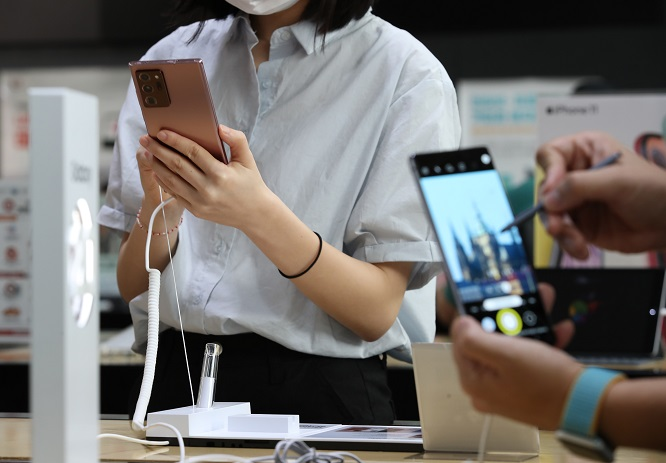 This file photo taken on Aug. 6, 2020, shows people checking Samsung Electronics Co.'s latest phablet, the Galaxy Note 20, at a store in Seoul. (Yonhap)