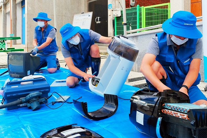 This photo, provided by Samsung Electronics Co. on Aug. 7, 2020, shows the company's service workers checking flood-damaged electronic products to help victims of heavy rains in Yeoncheon County, Gyeonggi Province.