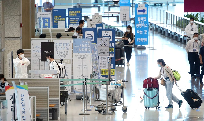 People arriving from abroad are guided to undergo a quarantine procedure in the arrival hall at Incheon airport, west of Seoul, on Aug. 11, 2020. (Yonhap)