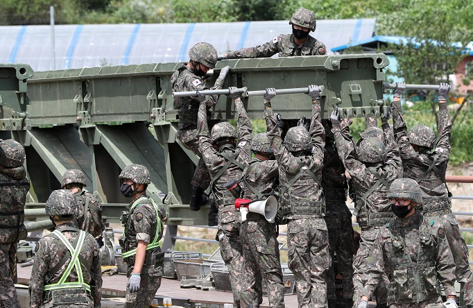 Engineering soldiers build a makeshift bridge on a flood-damaged bridge over a stream in Inje, a town in South Korea's northeast province of Gangwon, on Aug. 12, 2020, after residents living across the stream were stranded for a week following heavy rain in the region. (Yonhap)