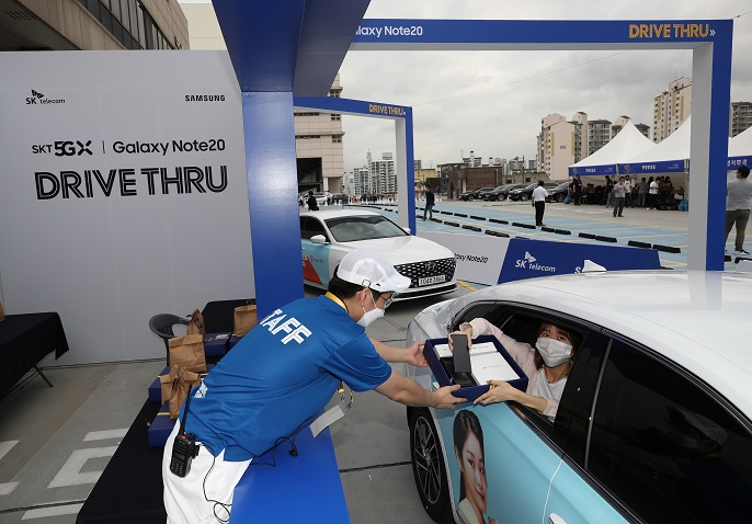 A customer receives Samsung Electronics Co.'s Galaxy Note 20 phone during SK Telecom Co.'s drive-through delivery event in eastern Seoul on Aug. 13, 2020. (Yonhap)