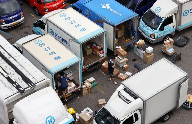 Delivery workers sort items that have to be delivered at a logistics center in Seoul on Aug. 13, 2020, a day before the industry went on a one-day special holiday. (Yonhap)