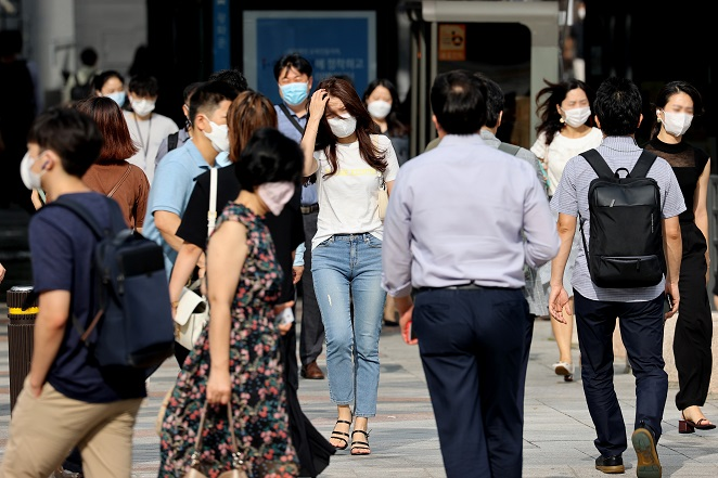 People wearing masks report to work at Gwanghwamun Square in Seoul on Aug. 19, 2020, as the coronavirus rages again in the country, especially in the Seoul metropolitan area. (Yonhap)