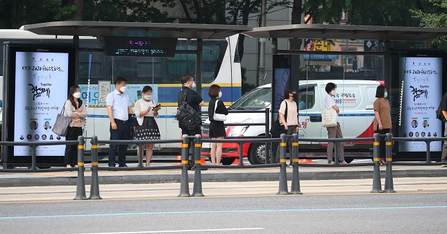 People wearing face masks wait for buses at a bus stop in Seoul on Aug. 25, 2020. (Yonhap)