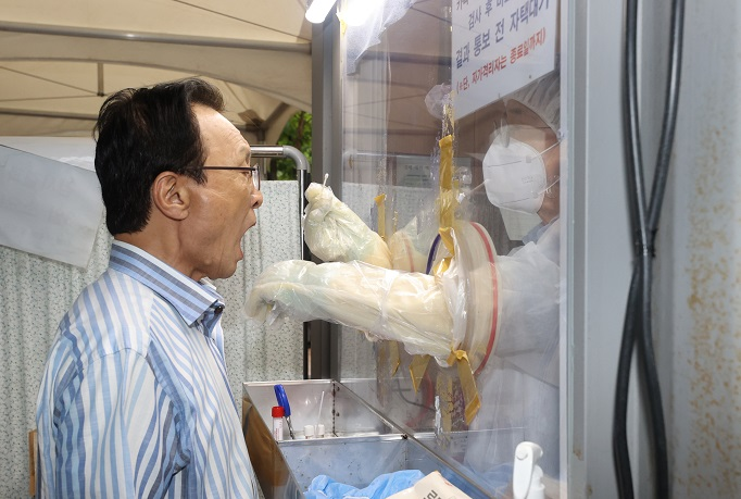 Lee Hae-chan, outgoing chief of the ruling Democratic Party, receives a polymerase chain reaction test at an outdoor clinic in Seoul's Yeongdeungpo Ward on Aug. 27, 2020, after a reporter covering him was confirmed to be infected with the new coronavirus. (Yonhap)