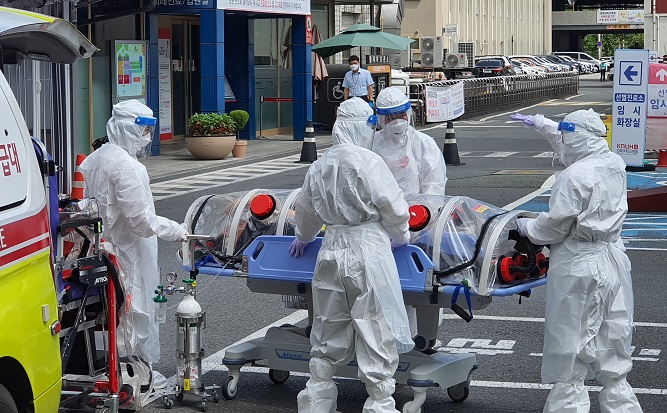 This photo taken by a Yonhap News TV reporter shows medical workers moving a confirmed patient of the new coronavirus to the Kyungpook National University Hospital in Daegu, 302 kilometers southeast of Seoul, on Aug. 30, 2020.