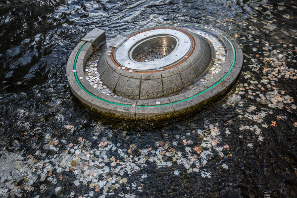 This photo, provided by the Seoul metropolitan government, shows coins tossed into a wishing well at Cheonggye Stream in the capital.