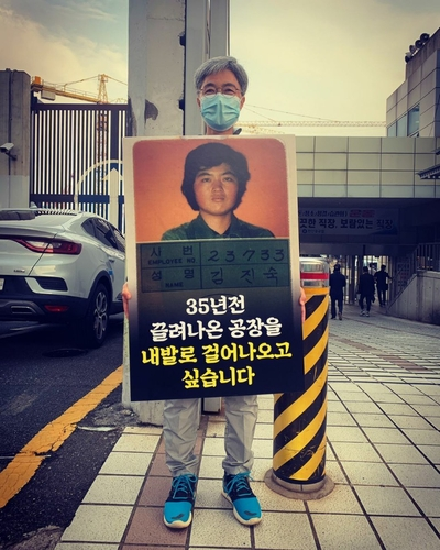 "Kim Jin-suk holds a picket that reads, ""I want to walk out of the shipyard where I was forcibly dragged out 35 years ago on my own feet,"" at the main gate of Hanjin Heavy Industries & Construction Co. in Busan, in this photo provided by her."